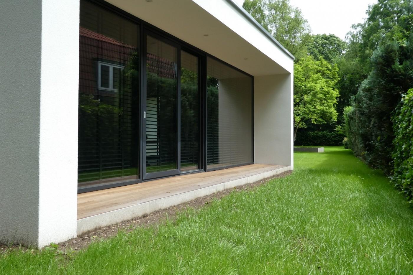De combinatie van gevel-sierpleister, houten terrasdelen en aluminium buitenkozijnen zorgt voor een fraai eindresultaat.